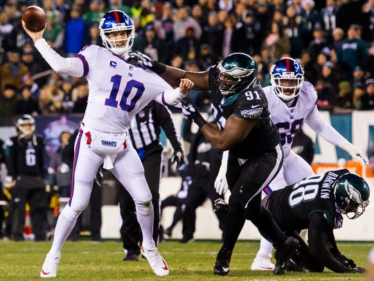 Eagles defensive tackle Fletcher Cox (No. 91) grabs ahold of Giants quarterback Eli Manning in the first quarter of an NFL game between the Philadelphia Eagles and the New York Giants at Lincoln Financial Field in Philadelphia, Pa. on Thursday night.