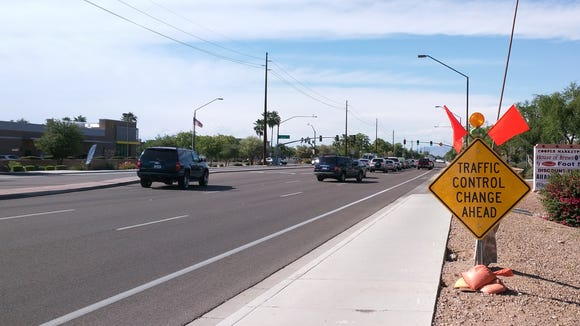 A traffic control change sign warns drivers of the new left-turn signal timing at Cooper and Warner roads in Gilbert.