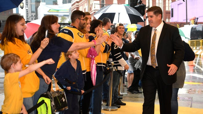 Predators coach Peter Laviolette slaps hands with fans during the Predators' Gold Walk on Lower Broadway Tuesday, Oct. 10, 2017 in Nashville, Tenn. .