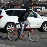 A bicyclist and car pass through the intersection at West Elizabeth Street and City Park Avenue. Fort Collins officials are looking at options for improving transportation systems on the West Elizabeth Corridor.