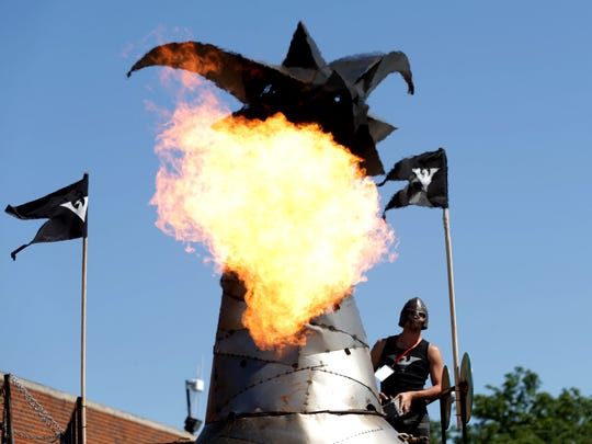 Kevin Bracken, 30, of Toronto, Ontario, Canada triggers the flames on his Heavy Meta dragon during Maker Faire Detroit at The Henry Ford in Dearborn, Michigan on Saturday, July 29, 2017.The dragon that took 20 people over 6 hours to build is 30 feet long and 19 feet high and is one of the popular attractions for people to stop by and watch.The two day event has everything from various inventions to power wheels racing, games for kids and many hands on activities.