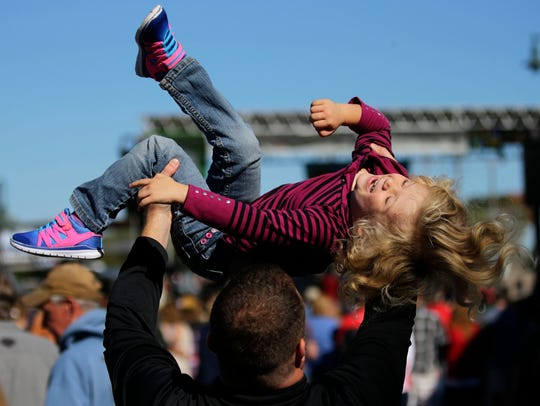 Michael Priscal of Neenah lifts his daughter, Haley,