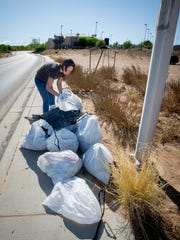 NMSU Senior, and Vice-President of the university's Earth Science Student Organization, Dhante Stroud, piles up bags filled with trash collected from an empty lot behind the Sonic Drive-In on Foothills Rd as part of the Great American Cleanup, April 9, 2016.