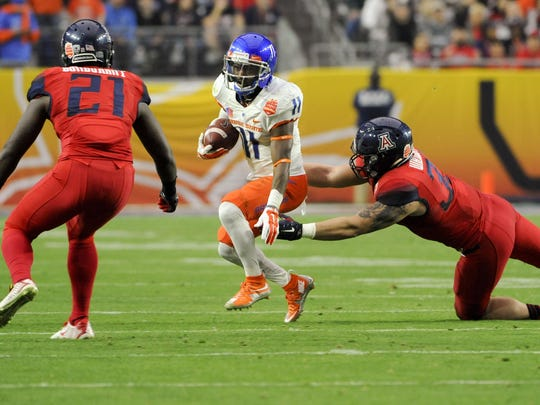 Boise State Broncos wide receiver Shane Williams-Rhodes (11) runs the ball under pressure from Arizona Wildcats linebacker Scooby Wright III (33) during the first quarter of the 2014 Fiesta Bowl at Phoenix Stadium.