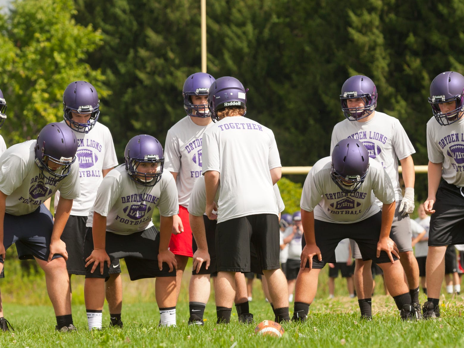 The Dryden High School football team prepares to run a play Monday morning during the first day of practice for fall sports.