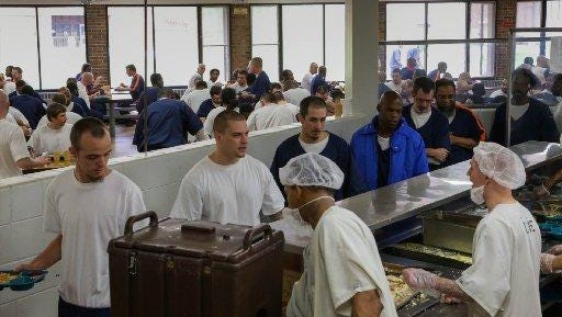 Inmates supervised by Aramark serve meals at a Michigan prison in 2014.