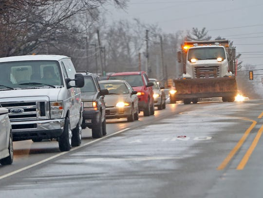 A DPW ice truck moves north on Michigan Road on Jan. 24, 2018.