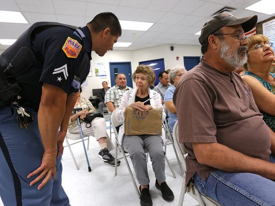 El Paso Police Area Representative Officer Eric Castaneda of the Central Regional Command Center talks with Corbin/Sambrano Neighborhood Association President Shirley Neagle during a July 24 meeting at the Seville Recreation Center.