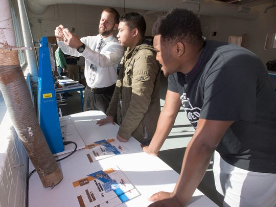Escambia County School district Workforce education curriculum specialist, Steven Harrell, left, gives Pensacola High School students, Olygen Quizon, center, and Kadarrious Lewis a demonstration on gear ratios and the manufacturing process.