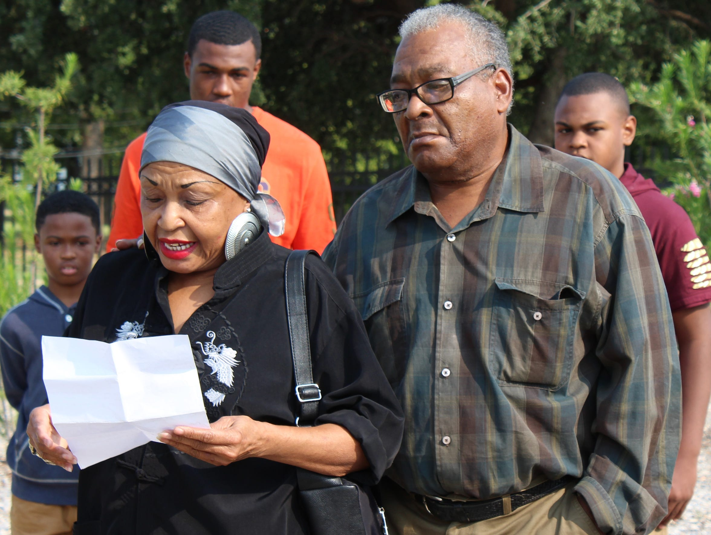 Mary Dansby, left, reads a poem about the life her