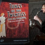 """Robert Rawlins, a Rowan University music professor, holds a copy of his new book, """"Tunes of the Twenties' and a soprano sax from 1924, in his Clayton home."""