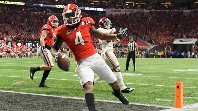 Georgia Bulldogs wide receiver Mecole Hardman (4) runs the ball for a touchdown during the second quarter against the Alabama Crimson Tide in the 2018 CFP national championship college football game at Mercedes-Benz Stadium.