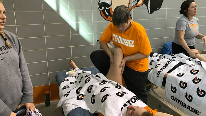 University of Tennessee massage therapist Robin Boughey works on UT swimmer Madeline Tegner during the SEC Swimming and Diving Championships on Friday at the Allan Jones Intercollegiate Aquatic Center.