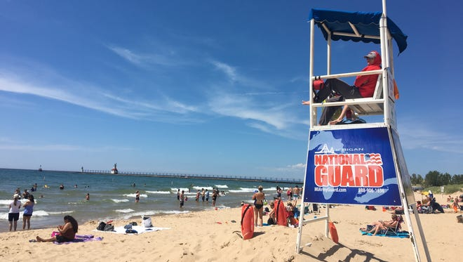 Two lifeguards watch Silver Beach County Park on June 16, 2017 in St. Joseph along Lake Michigan, where a yellow flag is raised, advising caution to swimmers in the water.