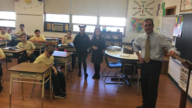 Our Lady of Perpetual Help Principal Carl Jankowski stands with kids in a classroom during a live feed on Facebook with the Courier Post.