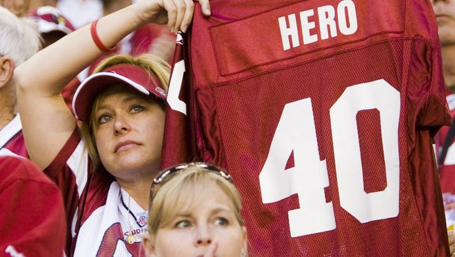 Sue Henderson from Mesa holds up Pat Tillman's numbered jersey during a halftime ceremony honoring the fallen soldier at University of Phoenix Stadium in Glendale on Sunday, Nov. 12, 2006.