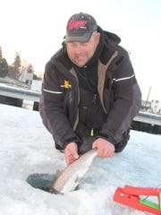 Ken Poludnianyk of Milwaukee releases a brown trout caught while ice fishing in the Kenosha harbor.