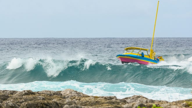 The crew of a parasailing vessel times its entrance into the Hagåtña boat basin as waves crash onto the reef on Nov. 18.