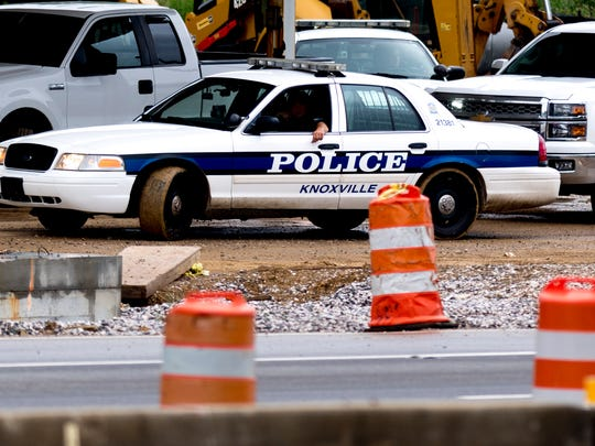 A Knoxville police officer patrols with another seen in the background as construction continues along Alcoa Highway between Woodson and Maloney Road in Knoxville on Wednesday, May 30, 2018.