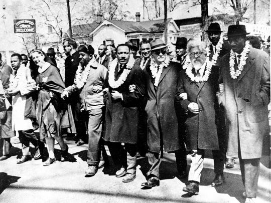 Dr. Martin Luther King Jr. links arms with other civil rights leaders as they begin the march to the state capitol in Montgomery from Selma, Ala. on March 21, 1965. The demonstrators are marching for voter registration rights for blacks. Accompanying Dr. Martin Luther King Jr. (fourth from right), are on his left Ralph Bunche, undersecretary of the United Nations, Rabbi Abraham Joshua Heschel, and Rev. Fred Shuttlesworth. They are wearing leis given by a Hawaiian group.  (AP Photo)