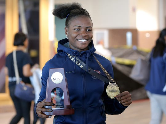 UTEP's Tobi Amusan holds her gold medal and trophy at the El Paso International Airport after arriving Sunday from the NCAA Track and Field Championships in Oregon. Amusan won the national championship in the 100-meter hurdles.