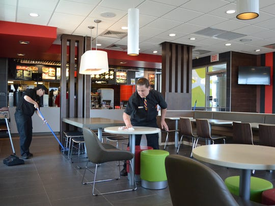 McDonald's employees in Oconto wipe down tables and sweep the newly renovated dining area, which features a section of soft seats.