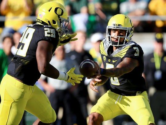 Oregon quarterback Vernon Adams Jr. (3) hands off the