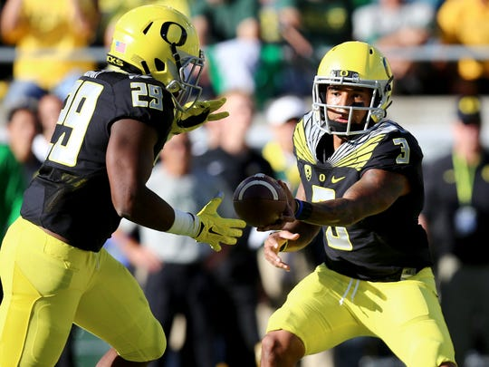 Oregon quarterback Vernon Adams Jr. (3) hands off the football to running back Kani Benoit (29) during the first quarter of an NCAA college football game against Eastern Washington, Saturday, Sept. 5, 2015, in Eugene, Ore. (AP Photo/Ryan Kang) ORG XMIT: ORRK104