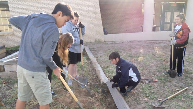 Lynn Middle School students and members of the local Kiwanis Club work on a project at the school.