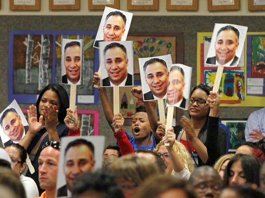 Rey Arizmendi, 13, an eighth-grader at Monroe High School, center, joins friends and family in holding up photos of Monroe principal Armando Ramirez as a sign of support for him at the Rochester School District board meeting Thursday in Rochester. The board was considering removing Ramirez as principal of the school.