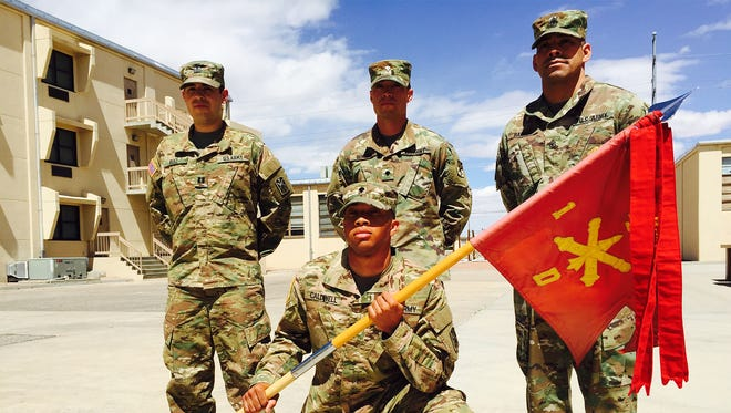 From left, Capt. Daniel Ruiz, Spc. Elmo Caldwell with battery guidon, Spc. Jonathan Benitez standing and 1st Sgt. Tomas Barrios, far right, are in the courtyard near Delta Battery's headquarters at Fort Bliss.