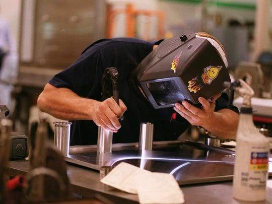 A worker at Central States Industrial welds flow panels used in food processing equipment in this 1999 photo.