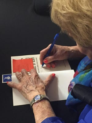 Holocaust survivor Eva Mozes Kor signs a book before speaking Tuesday at Indiana University East. More than 400 people attended and she sold out of books.