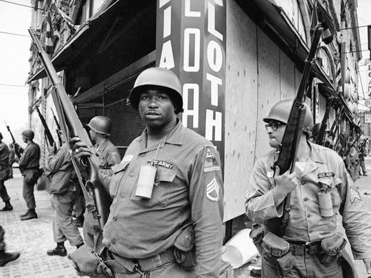 In this July 14, 1967, file photo, National Guardsmen stand at the corner of Springfield Avenue and Mercer Street in Newark, where four days of deadly violence and looting came to be known as the Newark riots.
