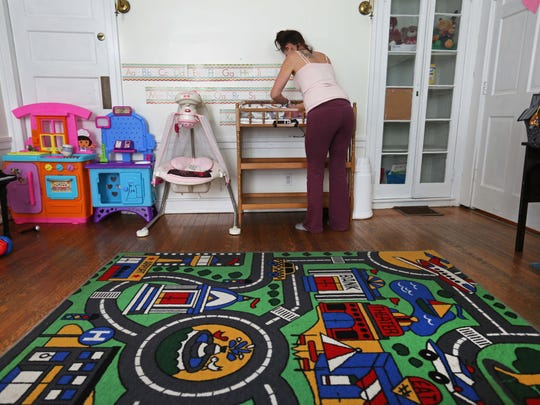 A mother recovering from addiction changes the diaper of a newborn baby while staying at Connections Women's and Children Sober Living house in Milford.