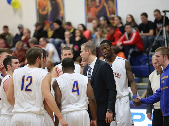 Madonna University men's basketball head coach Noel Emenhiser talks to his team during a timeout. Emenhiser and his coaching staff comb area high schools for talent.