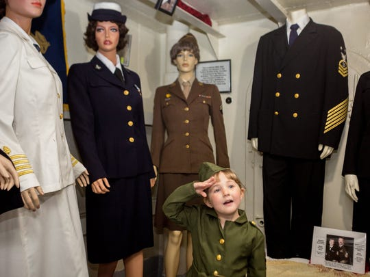 Hope Arends, 4, of Muskegon salutes to her mother while posing for a portrait aboard the USS LST 393 Veterans Museum in downtown Muskegon on May 13, 2018. Arends is dressed in WWII Army Corps feminine wear.