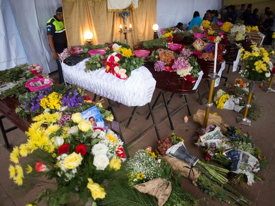 Los dolientes lloraban por la tarde sobre varios ataúdes colocados en fila en el principal parque de San Juan Alotenango.