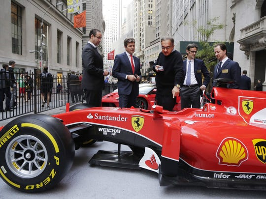 Sergio Marchionne, center, CEO of Fiat Chrysler, points to a Ferrari SF15-T parked in front of the New York Stock Exchange in honor of Ferrari's initial public offering of stock in October 2015.