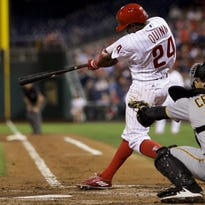 Philadelphia Phillies' Roman Quinn, left, follows through after hitting a two-run double off Pittsburgh Pirates starting pitcher Gerrit Cole during the second inning of a baseball game, Monday, Sept. 12, 2016, in Philadelphia. Pirates catcher Francisco Cervelli, right, looks on. (AP Photo/Matt Slocum)