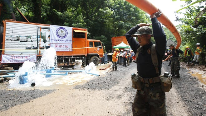 Thai soldiers carry drainpipe July 4 toward the cave where a youth soccer team and its assistant coach have been trapped by water.
