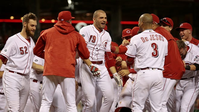 Cincinnati Reds first baseman Joey Votto (19) is mobbed at home plate by his teammates after hitting a walk-off solo home run in the bottom of the ninth inning of the MLB National League game between the Cincinnati Reds and the St. Louis Cardinals at Great American Ball Park on Tuesday, June 7, 2016.