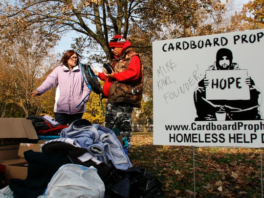 Cardboard Prophets volunteer Kitty Henry of Lansing chats with a Lansing area homeless man Tuesday, Nov. 14, 2017, at Reutter Park in downtown Lansing. The organization set up tables with water and snacks, and brought boxes of winter wear, shoes, and boots for those in need. The city of Lansing now requires permits for such activities.