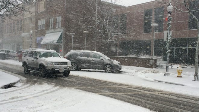 Drivers travel down a snow-covered Main Street Monday afternoon in downtown Stevens Point.