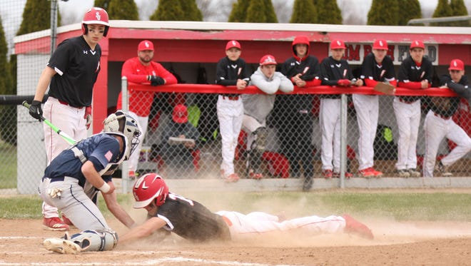 SJCC's Logan Black is tagged out by Woodmore's Mitchell Miller. Black was caught trying to steal home on a play in the first inning.