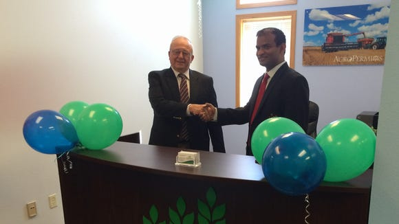Madhu Jamallamudi, founder of Agrometrics and AgroPermits, shakes hands with Louis Wysocki of Wysocki Family of Companies at his new office in the Portage County Business Park on July 25, 2016.