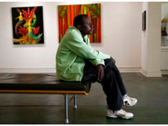 This April 11, 2017 combo shows William Hardy, who is homeless, posing for a portrait both at the Lemieux Galleries, left, and where he sleeps with a crate and a cardboard box under the Pontchartrain Expressway in New Orleans. Hardy was given a camera and has sold prints in the gallery. His works are part of an exhibit by artists, who are or were previously homeless, currently on display at LeMieux Galleries in New Orleans' Arts District. The show, which opened April 1, runs through Saturday, April 15.