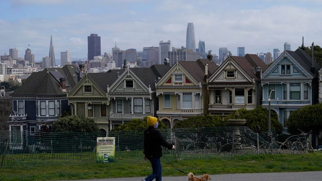 "A pedestrian wearing a mask walks a dog along a path in front of the ""Painted Ladies,"" a row of famed Victorian homes, and the San Francisco skyline at Alamo Square Park on Saturday."
