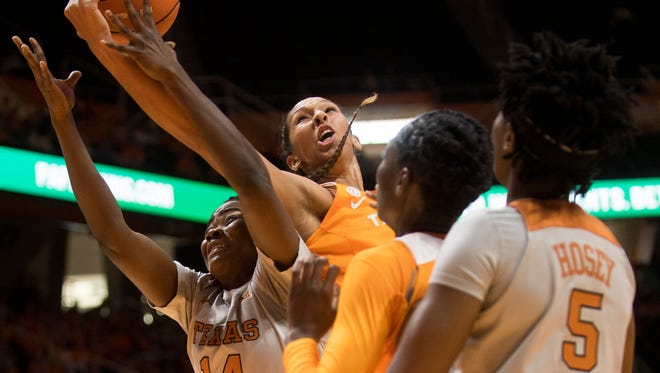 Tennessee center Mercedes Russell (21) and Texas forward Olamide Aborowa (14) fight for a rebound Sunday.