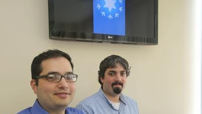 """Brothers Ronnie, left, and Barry Schwartz, chief technical officer and chief executive officer of RedBrick, a web and mobile development company in West Nyack, have developed an app called """"Minyan Now"""". The app allows religious Jews to connect anywhere in order to bring together the needed ten Jews necessary to form a prayer minyan. A minyan is a quorum of ten Jewish adults required for certain religious obligations. The two were photographed July 9, 2014 with a screen image of their app's home screen behind them."""